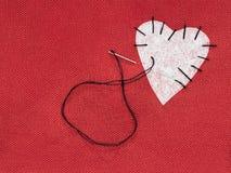 Gewebeherzrot mit weißem Flecken und schwarzem Nähgarn Bessern Sie Konzept des defekten Herzens aus lizenzfreie stockfotos