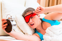 Gewecktes Mädchen betrachtet einen Wecker Stockbild