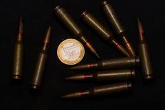 Geweer munitie rond één euro muntstuk op zwarte achtergrond Symboliseert de oorlog voor geld en één van de wereld` s problemen stock foto's