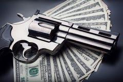 Gewehr auf dem Hintergrund mit 100 Dollars Stockfotos