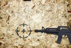 Gewehr und Ziel auf hölzernem Hintergrund Lizenzfreies Stockfoto