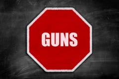 Gewehre geschrieben auf ein Stoppschild auf einer schwarzen Tafel Stockbilder