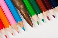 Gewehrgewehrkugel, die in einer Reihe mit Bleistiften liegt Lizenzfreies Stockbild