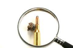 Gewehrkugel unter Vergrößerungsglas Stockfotos