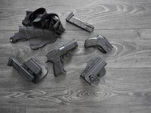 Gewehrschwarzes, Reservemagazine und lederner Pistolenhalfter auf grauem Hintergrund stockbild