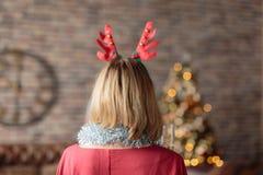 Geweih-Rotwildstirnband der Frau tragendes, das verzierten Weihnachtsbaum betrachtet Hintere Ansicht stockfoto