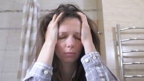 Gewekte vermoeide vrouw in de badkamers met kater en hoofdpijn stock footage