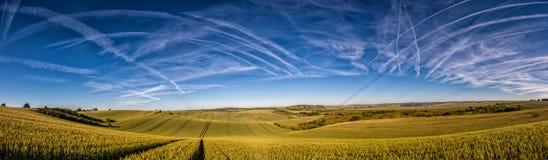 Gewellte Märchenfrühlingslandschaft mit Feldern und Contrails chemtrails auf dem Himmel Lizenzfreie Stockbilder