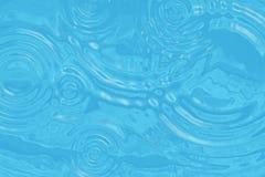 Gewellte Türkiswasseroberfläche mit Kreisen von Tropfen Lizenzfreies Stockbild