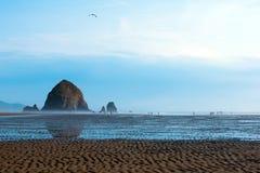 Gewellter Sand mit gewelltem Wasser auf Weise zum enormen Felsen Stockfotografie