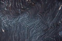 Gewelltes Profil, wie Kreise auf dem Wasser auf einem dunklen Naturstein nannte Quarzit Rosso Luana lizenzfreies stockfoto