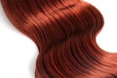 Gewelltes rotes Haar auf wei?em Hintergrund lizenzfreie stockbilder