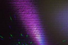 Geweven bakstenen muur die door gekleurde lichten wordt aangestoken Stock Afbeelding