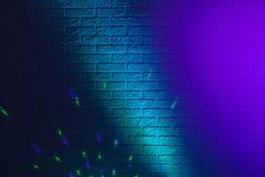 Geweven bakstenen muur die door gekleurde lichten wordt aangestoken Stock Foto