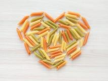 Geweven Italiaanse voedselachtergrond - kleurrijke ongekookte het hartvorm van pennedeegwaren op houten lijst royalty-vrije stock fotografie