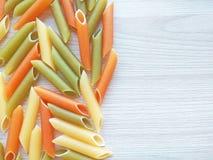 Geweven Italiaanse voedselachtergrond - kleurrijke ongekookte pennedeegwaren op houten lijst stock foto's