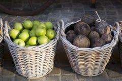 Geweven manden met groene appelen en kokosnoten royalty-vrije stock foto