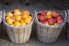 Geweven manden met rode appelen en sinaasappelen stock afbeelding