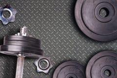 Gewichte am Turnhalle Whit Griff und dem Barbell Stel-Turnhallenausrüstung auf Metallbodenhintergrund Lizenzfreies Stockfoto