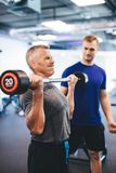 Gewichtheben des älteren Mannes, unterstützt vom persönlichen Trainer lizenzfreie stockfotos