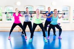 Gewichtheffen in de gymnastiek met domoren Stock Foto's