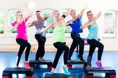 Gewichtheffen in de gymnastiek met stepper Royalty-vrije Stock Afbeeldingen