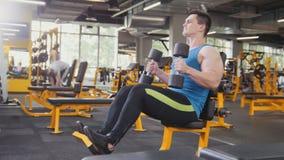 Gewichtheffen in de gymnastiek - de spieratleet voert opleiding voor bicepsen met domoren uit Royalty-vrije Stock Fotografie