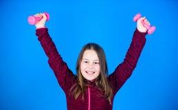 gewichtheffen voor muscules Kinderjarenactiviteit Gelukkig atletisch kind met barbell training van atletische kleine meisjesgreep stock afbeelding