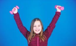 gewichtheffen voor muscules Kinderjarenactiviteit Gelukkig atletisch kind met barbell training van atletische kleine meisjesgreep stock afbeeldingen