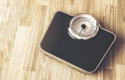 Gewichtsschaal op houten vloer Stock Afbeelding