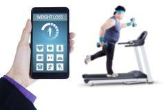 Gewichtsverlust-APP und Mann, die auf Tretmühle trainieren Stockbild