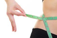 Gewichtsverlust. Grünes messendes Band auf Frauenkörper Stockfotografie