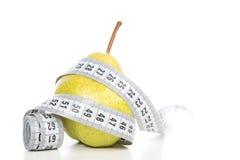 Gewichtsverlustkonzept der gesunden Diät mit Birne und Maßband Lizenzfreie Stockfotografie