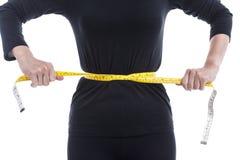 Gewichtsverlustkonzept, die Frau im Schwarzen versucht, ihr wais zu verringern Lizenzfreies Stockfoto