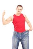 Gewichtsverlustmann, der Daumen aufgibt und eine alte Jeans hält Stockfotografie