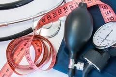 Gewichtszunahme oder Verlust und Hoch- oder Blutdruckkonzept Messendes Band, Stethoskop und Sphygmomanometer Effekt von Korpulenz lizenzfreie stockfotos