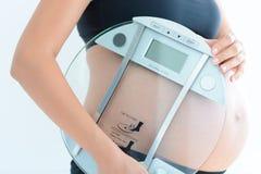 Gewichtszunahme während der Schwangerschaft mit Holdingskala der schwangeren Frau Stockfotografie