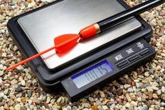 Gewichtung eines Schwimmers auf einer Taschenskala aus den steinigen Grund Lizenzfreie Stockfotos