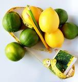 Gewichtverlust Frauentorso mit dem Maß, getrennt auf Weiß Messendes Band eingewickelt um Zitronen Lizenzfreie Stockbilder