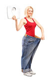 Gewichtverlustfrau, die eine Gewichtskala anhält lizenzfreie stockbilder