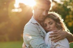 Gewidmete junge Paare, die unter der untergehenden Sonne umarmen Lizenzfreies Stockbild