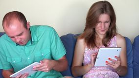 Gewijd man spel met tablet en het negeren van vrouw met haar eigen computer close-up stock footage