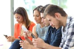 Gewijde groep vrienden die hun smartphones met behulp van royalty-vrije stock afbeeldingen