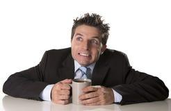 Gewijde zakenman in kostuum en bandholdingskop van koffie als maniak in cafeïneverslaving Royalty-vrije Stock Fotografie