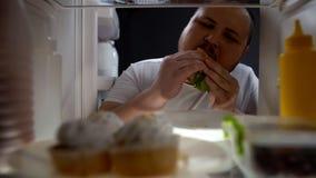 Gewijde zwaarlijvige mens die ongeduldig hamburger eten bij nacht, ongezonde voeding, dieet stock afbeelding