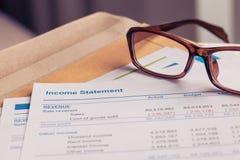 Gewinn- und Verlustrechnung Buchstabe auf braunem Umschlag und Brille, Geschäft Stockbild