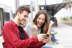 Gewinnende Online-Spiele des glücklichen Paars in einer Bahnstation stockfoto