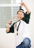Gewinnender Junge mit seiner Medaille und Trophäe Stockfotos