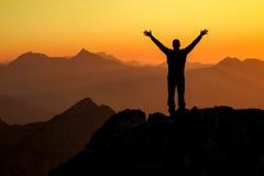 Gewinnender Mann des glücklichen Erfolgs auf Gipfel bewaffnet oben bei Sonnenuntergang Lizenzfreie Stockfotos