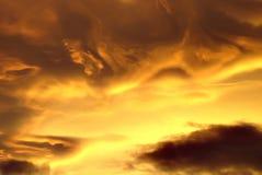 Gewirbelte gelbe und schwarze Wolken am Sonnenuntergang lizenzfreie stockfotos